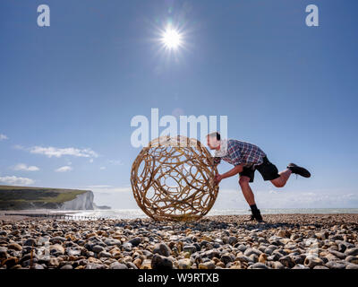 Cuckmere Haven, UK. 15 August, 2019.  Artist Keith Pettit places the first a series of steam-bent chestnut spheres on the beach at Cuckmere Haven in East Sussex. Made in collaboration with trug maker Charlie Groves, the complex shapes are inspired by the skeletal remains of ancient coccoliths - the calcium carbonate remains that make up the chalk of the South Downs. The exhibition 'What Lies Beneath' will be at the iconic coastguard cottages overlooking the Seven Sisters cliffs (pictured). Credit: Jim Holden/Alamy Live News - Stock Photo