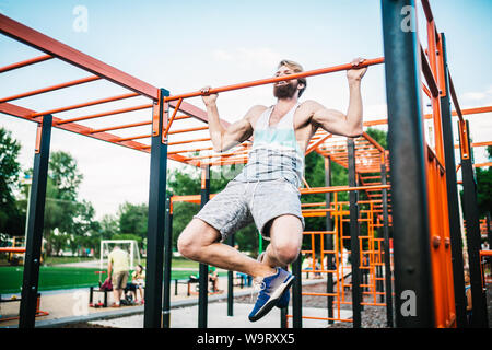 strong athlete doing pull-up on horizontal bar. Muscular man doing pull ups on horizontal bar in park. Gymnastic Bar During Workout. training strongma - Stock Photo