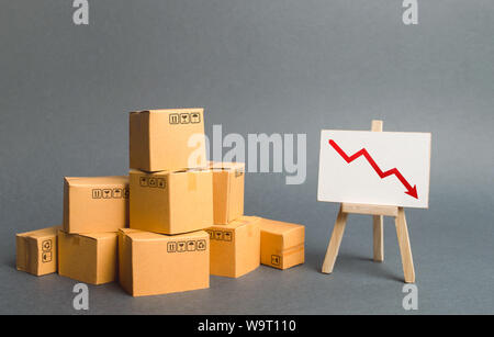 A pile of cardboard boxes and easel with red arrow down. Decrease in the quality, price, quantity and competitiveness of goods and products. Concept d - Stock Photo