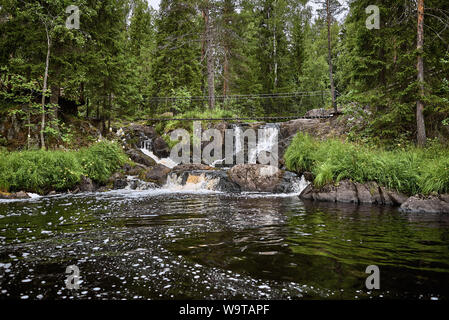 Multiple waterfalls and suspension bridge in the forest. Ruskeala park, Karelia. Nothern landscape, scenic view. Background for travel and adventure m - Stock Photo