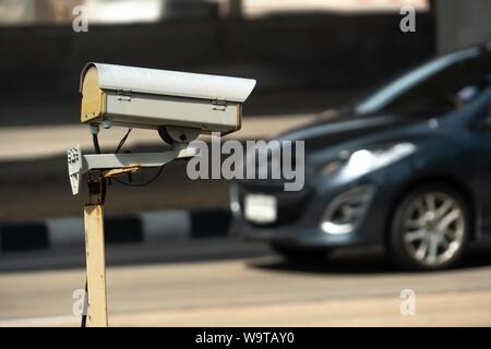 security monitoring CCTV camera mounted on old pole steel post. - Stock Photo