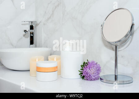 Set of natural cosmetics in beauty salon. Jars of body or hair care product on table with flowers. Space for text - Stock Photo