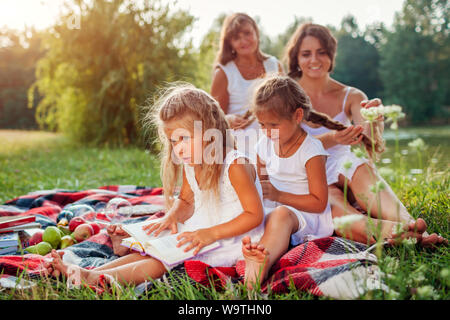 Mother, grandmother and kids weaving braids to each other while the youngest reads book. Family having fun during picnic in park. Three denerations - Stock Photo
