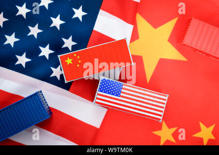 Miniature containers on flags of the USA and China, trade war