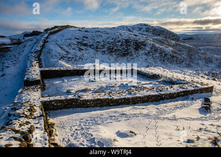 Winter snow lies on Hadrian's Wall and Milecastle 39 in the remote hills of Northumberland. - Stock Photo