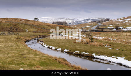 Patches of winter snow lie on pasture beside Widdale Beck river in Widdale valley near Hawes in England's Yorkshire Dales. - Stock Photo