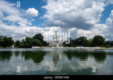 Wide angle view of the United States Capitol Building in Washington DC on a partly cloudy summer day, on the reflecting pool