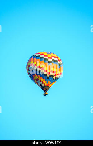 Colorful hot air balloon taking off with blue sky - Stock Photo