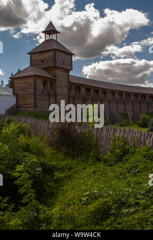Bottom view of an old wooden fortress with a high watchtower against blue cloudy sky, selective focus - Stock Photo