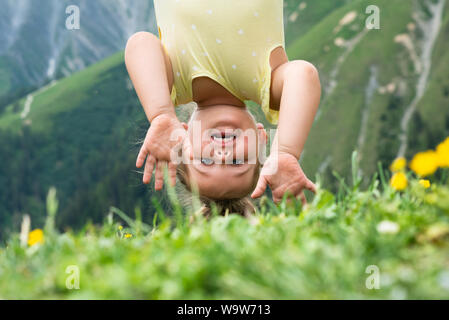 Little Girl Hanging Upside Down In Mountains - Stock Photo