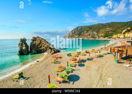 Chairs and umbrellas fill the Spiaggia di Fegina, the wide sandy beach in front of the old section of the village of Monterosso al Mare, Italy - Stock Photo