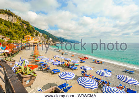 The sea and sandy beach Spiaggia di Fegina at the Cinque Terre Italy resort village of Monterosso al Mare with tourists enjoying the Italian Riviera - Stock Photo