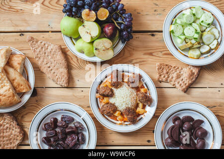 Table full with different foods. Yummy dinner table with fresh vegetables, fruits, bread and sweets. Different types of food - Stock Photo