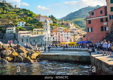 Tourists enjoy the sea, dock and village on a summer morning at the hillside city of Vernazza Italy, part of the Cinque Terre on the Italian Riviera - Stock Photo