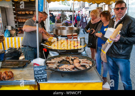 From open air street market in Dieppe, France. Hot food vendor offering paella and sausages fresh from the pan. - Stock Photo