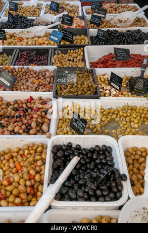 Trays with pickled olives, capers and sundried tomatoes at the open air street market in the centre of Dieppe, France. - Stock Photo