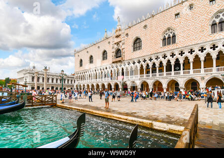 Tourists walk the Riva degli Schiavoni in front of by the Doge's Palace, Palazzo Ducale and St. Mark's Square along the grand canal in Venice, Italy - Stock Photo
