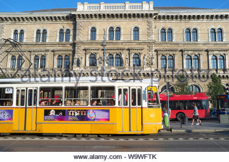 A tram passes the Corvinus University of Budapest, Hungary. - Stock Photo