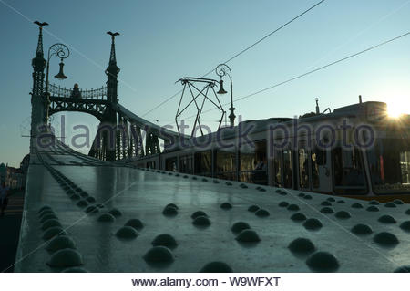 A silhouette view of a tram crossing the Szabadság híd (Liberty Bridge) in Budapest, Hungary. - Stock Photo
