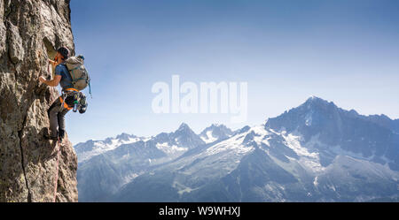 Young man rock climbing in Chamonix on the Clocher Clochetons Traverse on Brévent in front of a view of Mont Blanc. Aiguilles Rouges, French Alps.