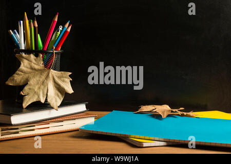 Books, notebooks, a pencil holder with pencils, pens and various school supplies, and some autumn leaves on wooden boards with a blackboard, in the ba - Stock Photo