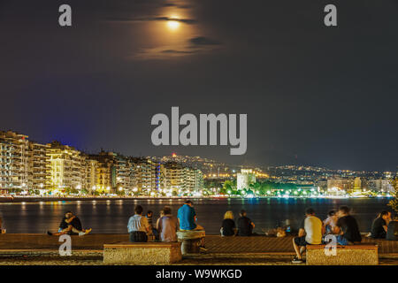 August full moon over Thessaloniki, Greece waterfront. 2019 summer moon rising over White Tower landmark, seen from the city port. - Stock Photo