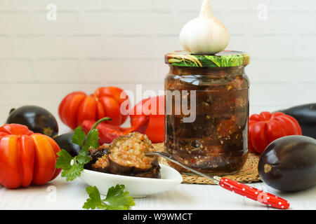 Eggplants in acute sauce of pepper, tomatoes and garlic in jar on the table, close-up, horizontal orientation, Harvesting vegetables for the winter - Stock Photo