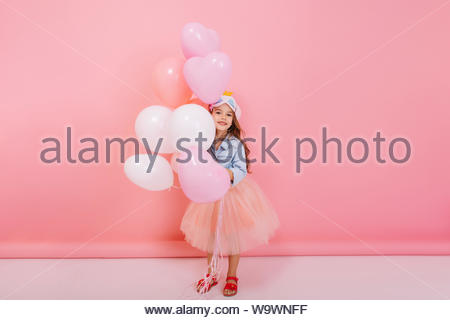 Joyful little girl in tulle skirt smiling to camera, having fun with flying balloons on pink background. Having birthday mood of pretty child, stylish outlook, expressing positivity - Stock Photo