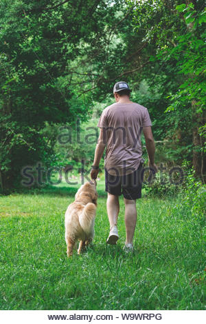 Man and dog walking on grass field - Stock Photo