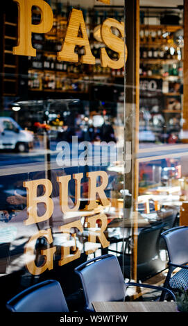Pasta and Burger inscription on the glass facade of modern restaurant in central Barcelona - Stock Photo