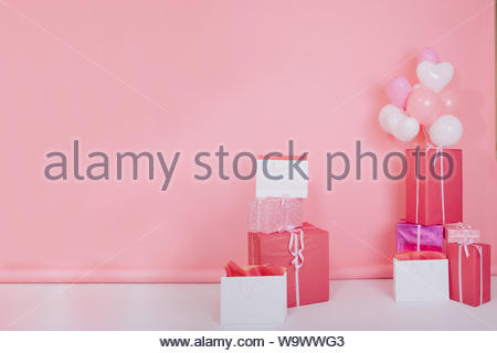 Photo of big bright presents and white party balloons for birthday standing on the floor. Colorful gift boxes with cute ribbons for christmas or st. valentines day isolated on rose-colored background - Stock Photo