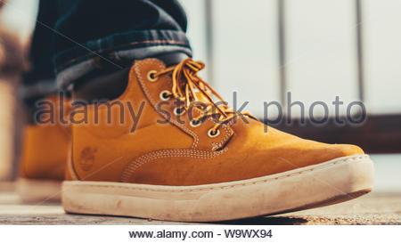 man wearing brown Timberland shoes - Stock Photo