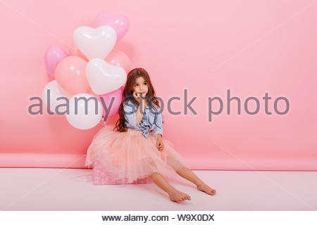 Amazing happy moments of young cute charming little girl with long brunette hair sitting on big present with flying balloons isolated on pink background. Expressing true emotions. Place for text - Stock Photo