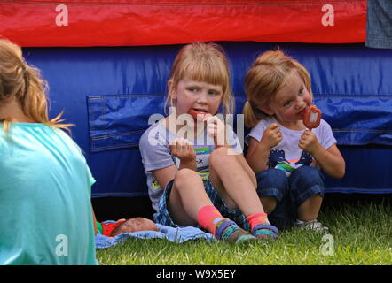 Verona, WI / USA - June 16, 2018: Two sisters enjoying posicles in the shade - Stock Photo
