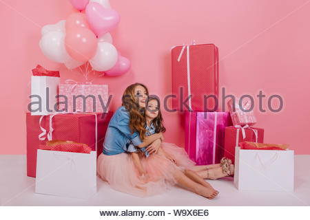 Excited curly young woman in retro jacket embracing her little barefooted daughter surrounded by colorful present boxes. Charming long-haired girl sitting on the floor with mom after birthday party - Stock Photo