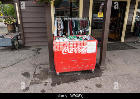 Red, vintage Coca Cola outside ice cooler / fridge holding sodas at the front of the store - Stock Photo