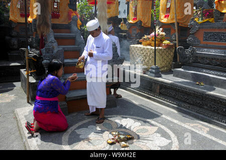 UBUD, BALI -JULY 24 2019:Hindu priest blessing Balinese family celebrating Galungan Kuningan holidays in a family temple in Ubud Bali, Indonesia. - Stock Photo