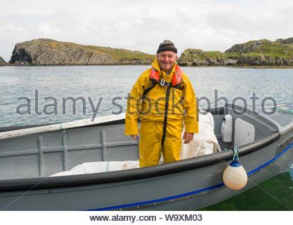 Irish man wearing yellow slicker rain suit and automatic inflating personal floatation device standing in small boat, Garnish Beach - Stock Photo