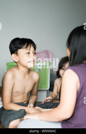 Children play in the room at home. Asian siblings plays together. - Stock Photo