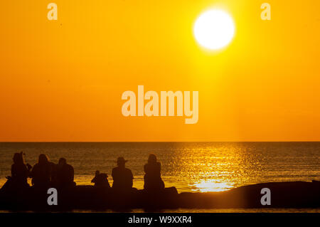 silhouette people seated on his back in a breakwater watching the sunset - Stock Photo