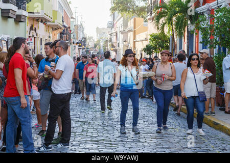 Tourists and locals explore out in streets with anticipation for the start of  San Sebastian Street Festival in Old San Juan, San Juan, Puerto Rico. - Stock Photo
