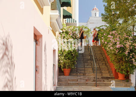 People chat on top of the flower filled stairs at Plaza de la Catedral located in front of San Juan Bautista Cathedral in Old San Juan, San Juan, PR.