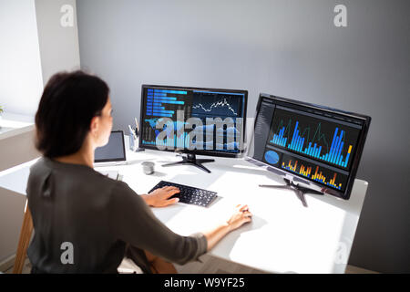 Young female stock market broker analyzing graph on computer at workplace - Stock Photo