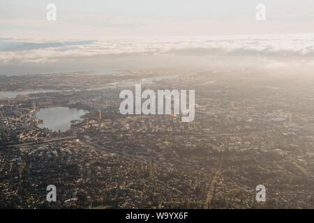 A distant aerial shot of a city with skyscrapers and a lake - Stock Photo