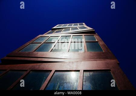 A low angle shot of a brutalist architectural brown high rise building - Stock Photo