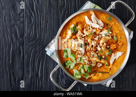 fragrant Indian Mulligatawny Soup is spiced with curry and made from creamy red lentils, carrots, apples and coconut milk, served in a metal saucepan - Stock Photo