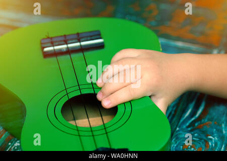 Kid hand holding a little ukulele - Stock Photo