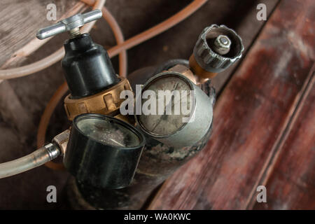 Pneumatic equipment close up. Manometers, valves, pressure vessel, pipes. Rustic weathered elements on soft focus background - Stock Photo