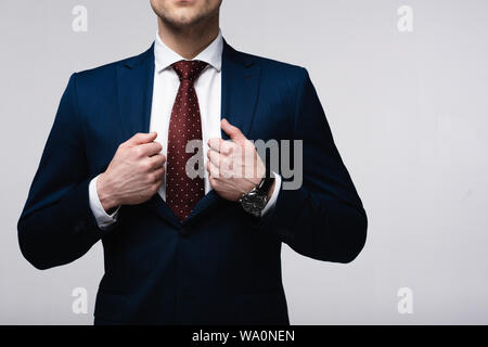 cropped view of confident businessman touching suit isolated on grey, human emotion and expression concept - Stock Photo