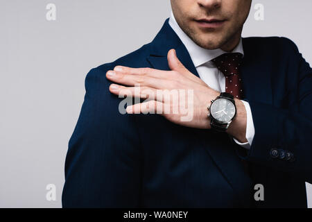 cropped view of businessman touching shoulder isolated on grey - Stock Photo